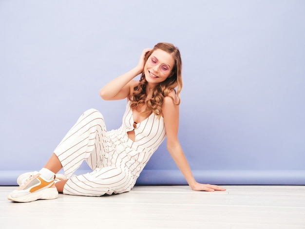 Młoda beztroska kobieta pozuje w pobliżu fioletowej ściany w studio