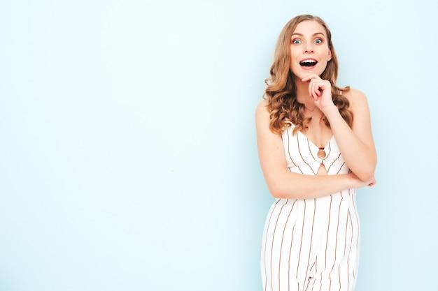 Młoda beztroska kobieta pozuje w pobliżu jasnoniebieskiej ściany w studio