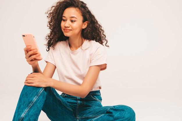 Młoda beztroska kobieta siedzi na szarej ścianie w studio