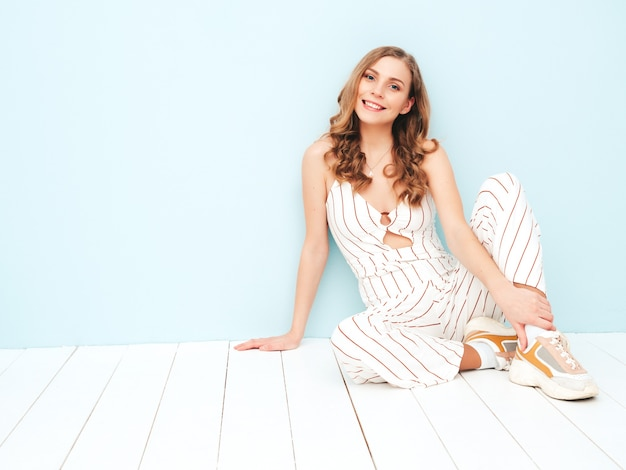 Młoda beztroska kobieta siedzi w pobliżu jasnoniebieskiej ściany w studio