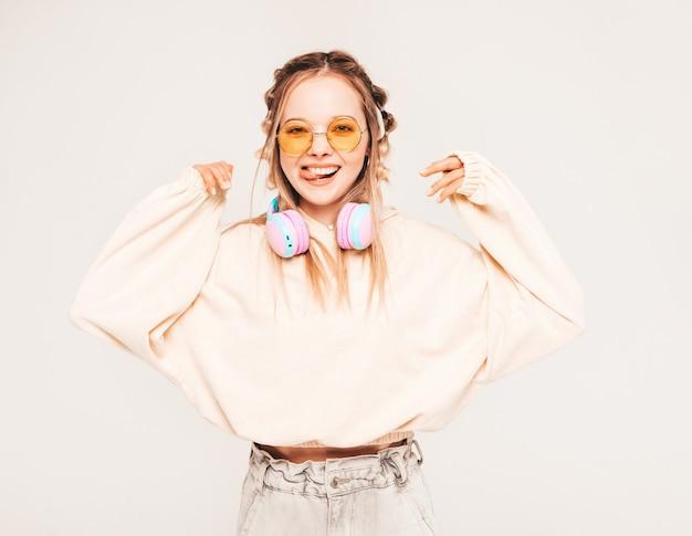 Młoda beztroska modelka słuchająca muzyki w słuchawkach bezprzewodowych
