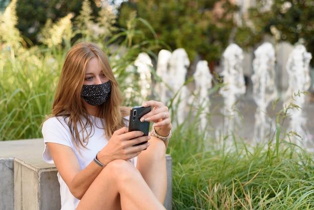 Młoda biała kobieta z maską patrząc przez telefon na ulicy