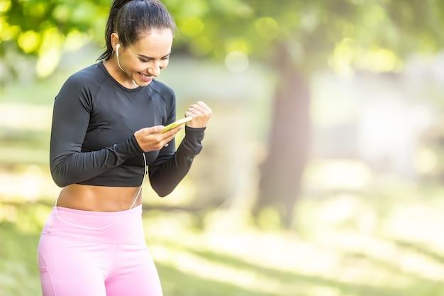 Młoda biegaczka jest zaskoczona swoimi wynikami sportowymi, które ogląda w aplikacji na smartfonie.
