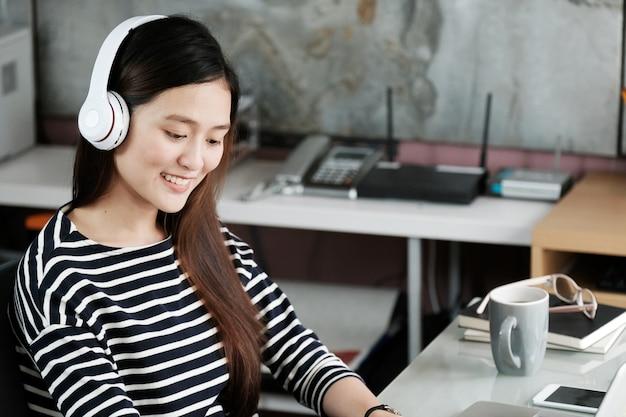 Młoda biurowa kobieta jest ubranym bezprzewodowych hełmofony relaksuje podczas gdy pracujący, biurowi style życia, ludzie i technologia ,.