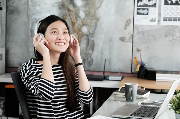 Młoda biurowa kobieta jest ubranym bezprzewodowych hełmofony relaksuje podczas gdy pracujący