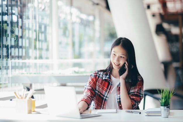 Młoda biurowa kobieta opowiada na telefonie komórkowym z klientem.