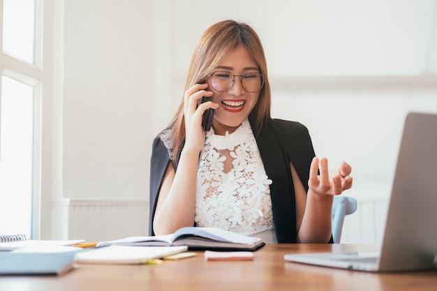 Młoda biurowa kobieta opowiada na telefonie komórkowym.