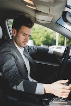 Młoda biznesmen chwytania przekładnia w samochodzie