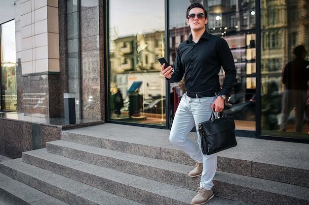 Młoda biznesmen poza. schodzi po schodach. facet trzyma telefon i czarną torbę. młody człowiek jest na zewnątrz.