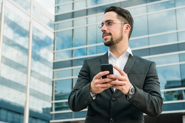 Młoda biznesmen pozycja przed budynku biurowego mienia telefonem komórkowym