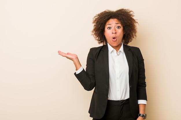 Młoda biznesowa amerykanin afrykańskiego pochodzenia kobieta imponująca mienie kopii przestrzeń na palmie.