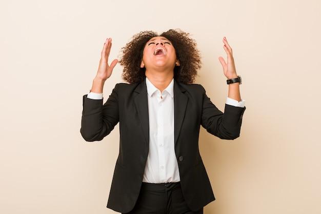 Młoda biznesowa amerykanin afrykańskiego pochodzenia kobieta krzyczy do nieba, przyglądający up, sfrustrowany.