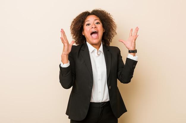 Młoda biznesowa amerykanin afrykańskiego pochodzenia kobieta świętuje zwycięstwo lub sukces, jest zdziwiony i zszokowany.