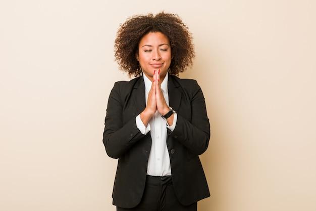 Młoda biznesowa amerykanin afrykańskiego pochodzenia kobieta trzyma ręki w modli się blisko usta, czuje ufnego.