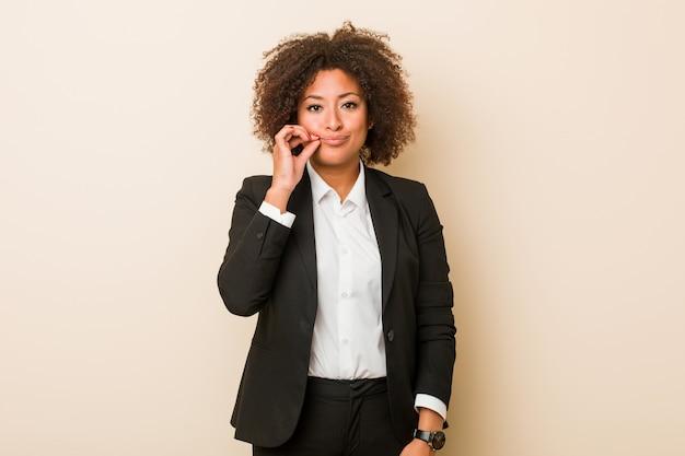 Młoda biznesowa amerykanin afrykańskiego pochodzenia kobieta utrzymuje sekret z palcami na wargach.