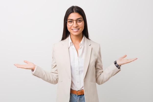 Młoda biznesowa arabska kobieta odizolowywająca przeciw białej ścianie pokazuje mile widziany wyrażenie.