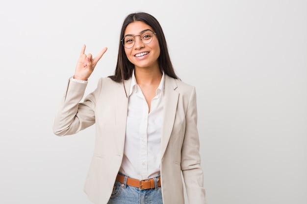 Młoda biznesowa arabska kobieta odizolowywająca przeciw białej ścianie pokazuje rogi gest jako rewoluci pojęcie.