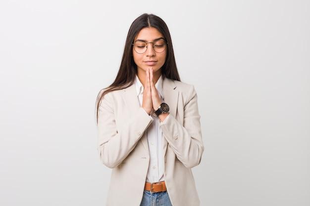 Młoda biznesowa arabska kobieta odizolowywająca przeciw białej ścianie trzyma ręki w modli się blisko usta, czuje się pewny.