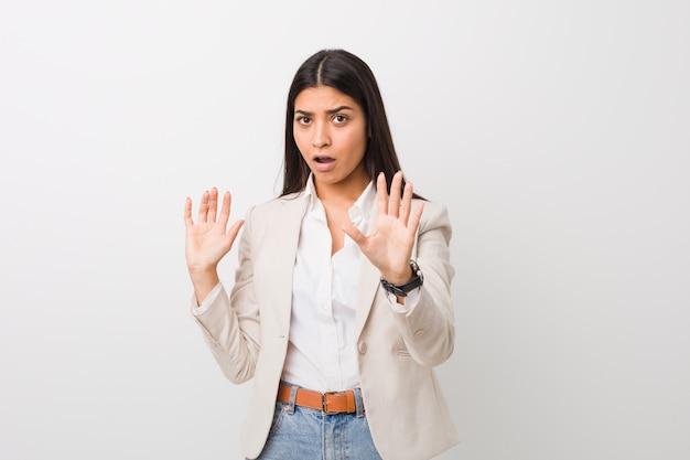 Młoda biznesowa arabska kobieta znowu na białym tle, będąc zszokowanym z powodu bezpośredniego niebezpieczeństwa