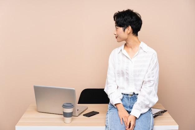 Młoda biznesowa azjatycka dziewczyna patrzeje z boku w jej miejscu pracy