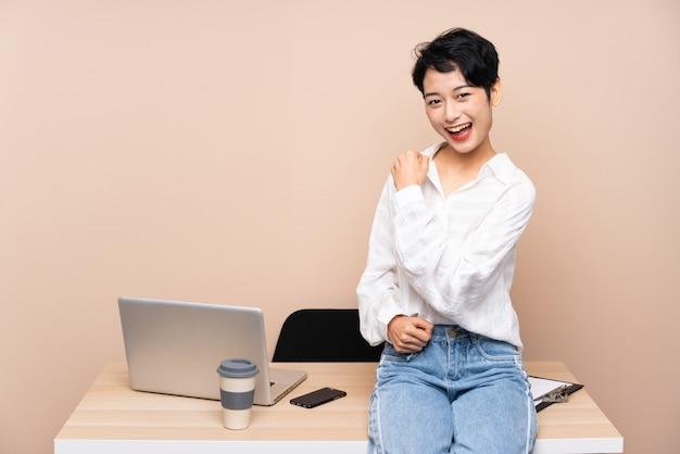 Młoda biznesowa azjatycka dziewczyna świętuje zwycięstwo w jej miejscu pracy