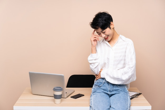 Młoda biznesowa azjatycka dziewczyna w jej miejsca pracy śmiać się
