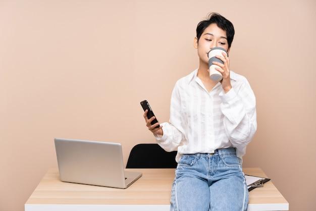 Młoda biznesowa azjatycka dziewczyna w jej miejscu pracy trzyma kawę tak