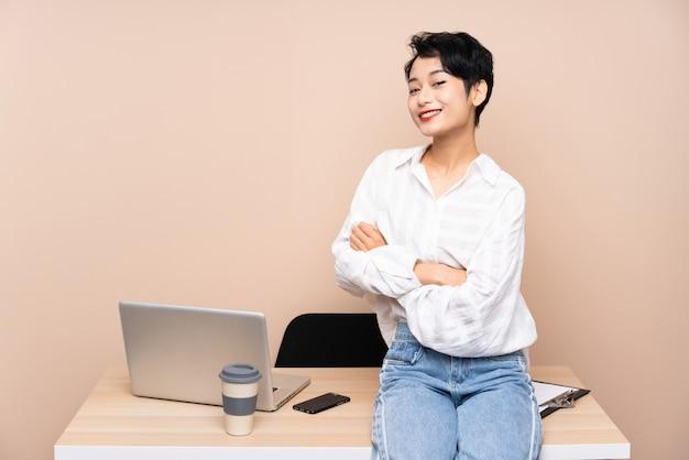 Młoda biznesowa azjatycka kobieta patrzeje z boku w jej miejscu pracy