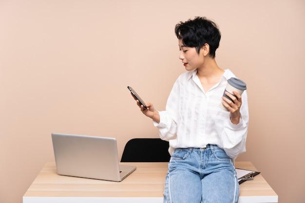 Młoda biznesowa azjatycka kobieta w jej miejscu pracy trzyma kawę tak