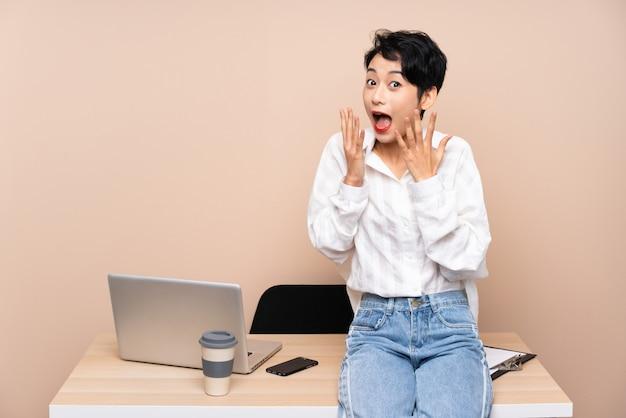 Młoda biznesowa azjatycka kobieta w jej miejscu pracy z niespodzianka wyrazem twarzy
