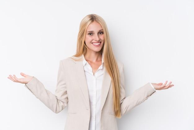 Młoda biznesowa blondynki kobieta na biel ścianie pokazuje mile widziany wyrażenie.