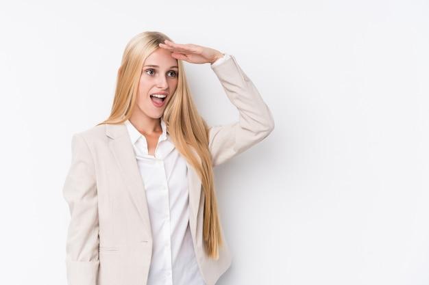 Młoda biznesowa blondynki kobieta patrzeje daleki utrzymuje rękę na czole na białym tle.
