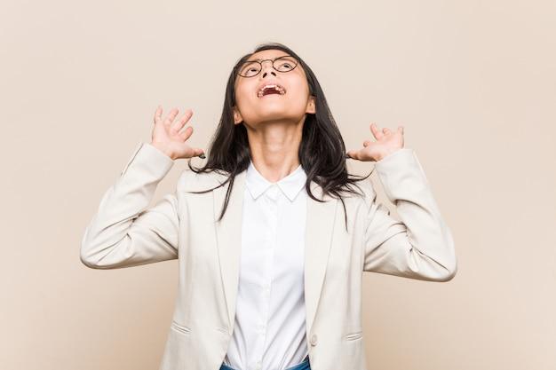 Młoda biznesowa chinka krzyczy do nieba, patrząc w górę, sfrustrowana.