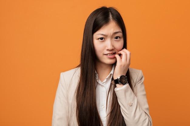 Młoda biznesowa chinka obgryzająca paznokcie, nerwowa i bardzo niespokojna.