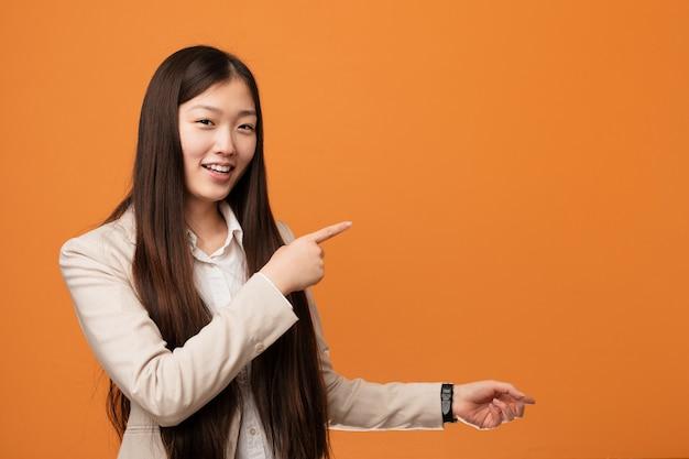 Młoda biznesowa chinka podekscytowana, wskazując palcami wskazującymi daleko.