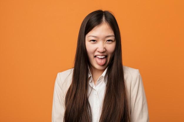 Młoda biznesowa chinka śmieszna i przyjazna wystaje mu język.