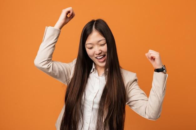 Młoda biznesowa chinka świętuje specjalny dzień, skacze i podnosi ręki z energią.