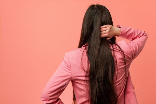 Młoda biznesowa chińska kobieta jest ubranym różowego kostium od behind myśleć o coś.