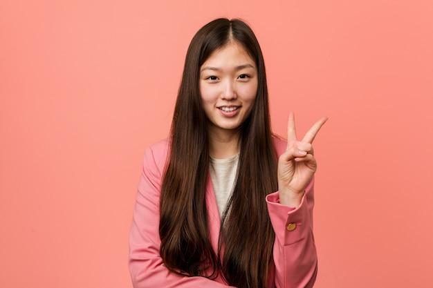 Młoda biznesowa chińska kobieta jest ubranym różowego kostium pokazuje numer dwa z palcami.