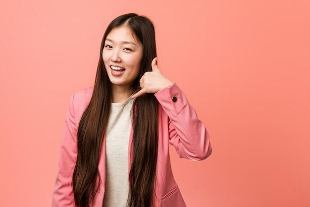 Młoda biznesowa chińska kobieta jest ubranym różowego kostium pokazuje telefon komórkowego wezwania gest z palcami.