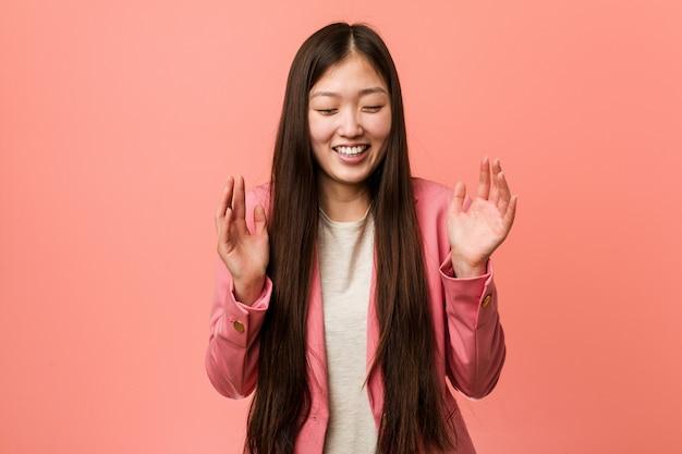 Młoda biznesowa chińska kobieta jest ubranym różowego kostium radosny śmiać się dużo.