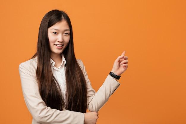 Młoda biznesowa chińska kobieta ono uśmiecha się radośnie wskazujący z palcem wskazującym daleko od.