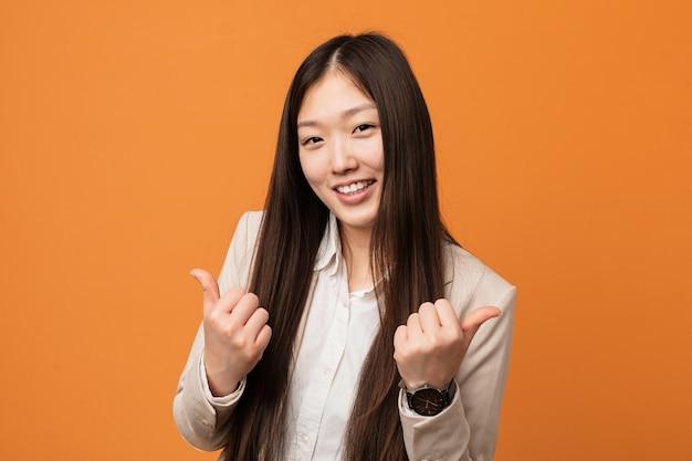 Młoda biznesowa chińska kobieta podnosi oba aprobaty, uśmiechnięty i ufny.