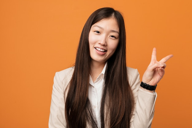 Młoda biznesowa chińska kobieta radosna i beztroska pokazuje pokoju symbol z palcami.