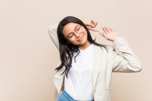Młoda biznesowa chińska kobieta rozciąga ręki, zrelaksowana pozycja.