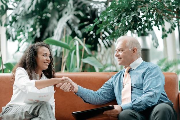 Młoda biznesowa dama ściska dłoń ze swoim partnerem biznesowym