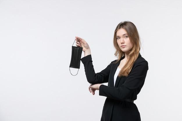 Młoda biznesowa dama w garniturze trzyma maskę medyczną i pozuje na odosobnionej białej ścianie