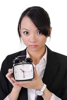 Młoda biznesowa dziewczyna trzyma jeden budzik i patrzy na ciebie na białym tle.