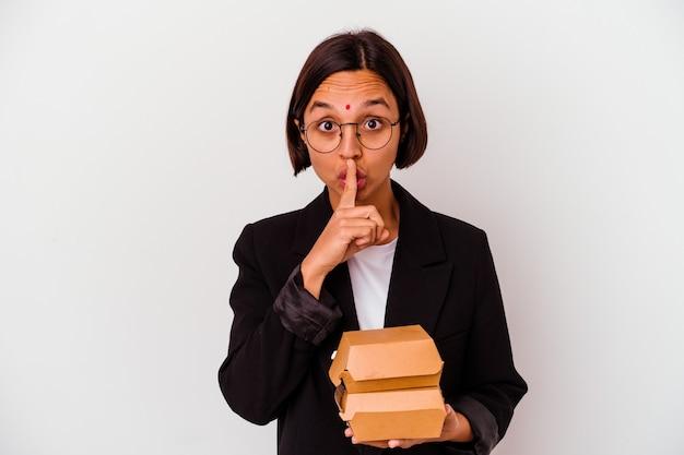 Młoda biznesowa indyjska kobieta je hamburgery na białym tle, zachowując tajemnicę lub prosząc o ciszę.