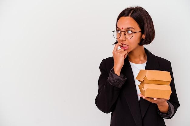 Młoda biznesowa indyjska kobieta je hamburgery na białym tle zrelaksowana myślenie o czymś patrząc na miejsce.